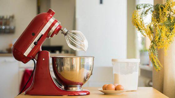 Ein Mixer von KitchenAid steht neben ein paar Eiern auf einem Küchentisch.