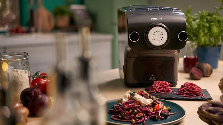 Die Nudelmaschine von Philips steht auf einem Küchentisch, davor zwei Teller mit fertig angerichteter Pasta.