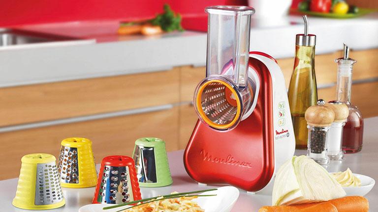 Der Zerkleiner von Moulinex steht zusammen mit mehreren Aufsätzen und verarbeitetem Gemüse auf einem Küchentisch.