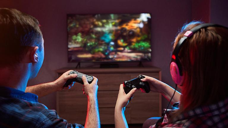 Zwei Personen sitzen mit Controllern in der Hand vor einem Fernseher und spielen zusammen ein Spiel.