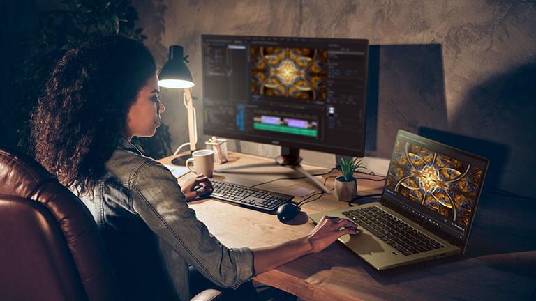 Eine Person sitzt an einem Schreibtisch. Mit der rechten Hand bedient sie ein Acer Swift 3X, mit der linken Hand eine externe Tastatur.