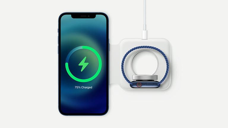 iPhone 12 und Apple Watch liegen auf einer Ladematte und laden auf.