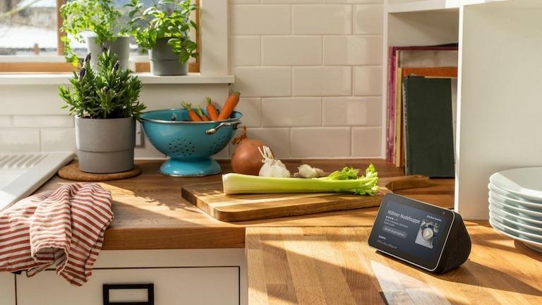 Das Amazon Echo Show steht in einer Küche. Im Hintergrund ist ein Schneidebrett mit Gemüse zu sehen. Das Gerät zeigt ein Rezept für Hühner-Nudelsuppe an.