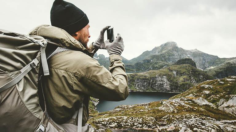 Ein Wanderer steht vor einem Berg. Mit seinem Smartphone nimmt er ein Bild der Szenerie auf.