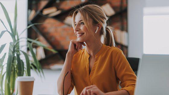 Eine Person sitzt am Schreibtisch und hat Bluetooth-Kopfhörer im Ohr. Sie lächelt und schaut dabei in den Raum.