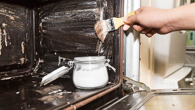 Eine Person streicht mit einem Pinsel den Backofen ein. Darin steht ein Glas mit weißem Pulver.