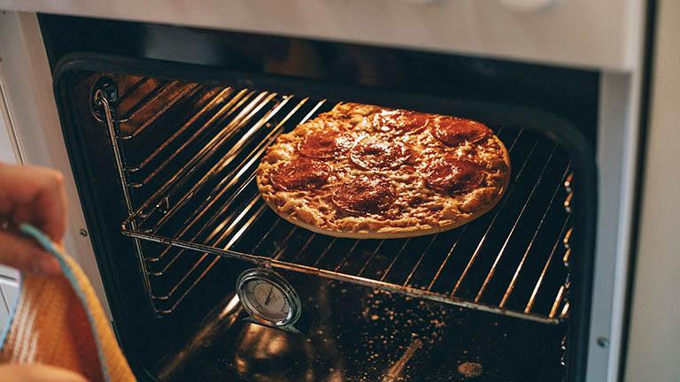Eine Person öffnet den Backofen. Darin ist eine fertige Pizza Salami zu sehen.