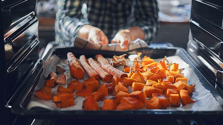 Eine Person holt ein Backblech aus dem Ofen. Darauf sind Karotten und mehr zu sehen.