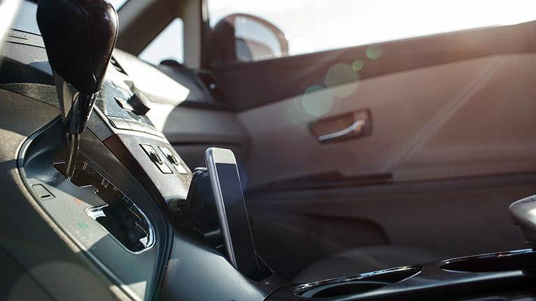 Blick ins Cockpit eines Autos. Zu sehen sind der Wählhebel einer Automatik und ein Smartphone.