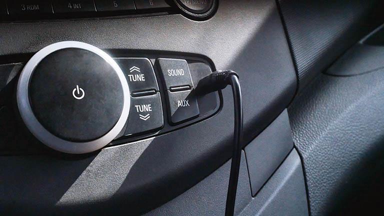 Ein Kabel steckt im AUX-Anschluss eines Autos.