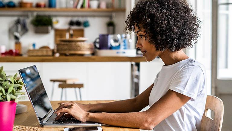 Eine Person sitzt vor einem Laptop und tippt auf der Tastatur.