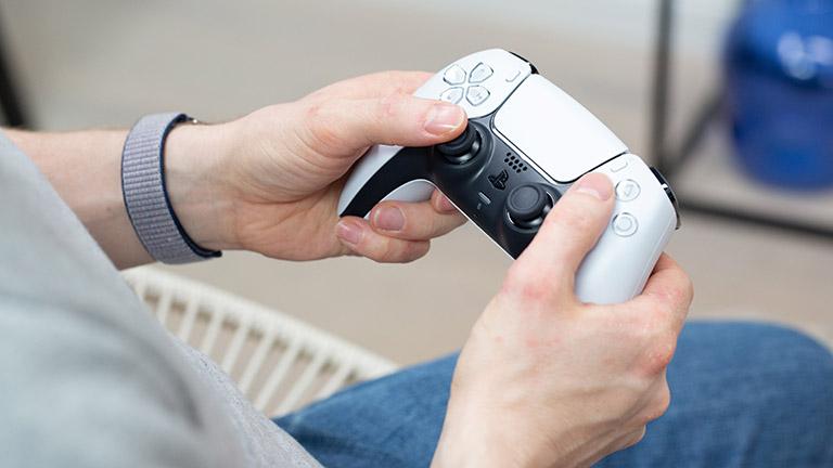 Eine Person hält den DualSense-Controller der PlayStation 5 leicht schräg ins Bild.
