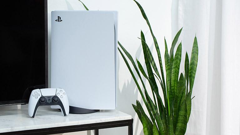 Die PlayStation 5 steht dekorativ auf einem Marmortisch neben einer Zimmerpflanzen. An die Konsole angelehnt steht der neue DualSense-Controller