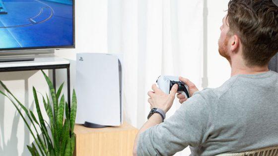 Eine Person sitzt vor einer PlayStation 5 und hält dabei den neuen DualSense-Controller in der Hand.
