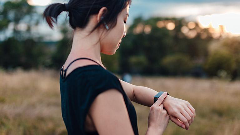 Eine junge Frau in kurzärmeligem T-Shirt steht in der Natur und bedient eine Apple Watch am Handgelenk.
