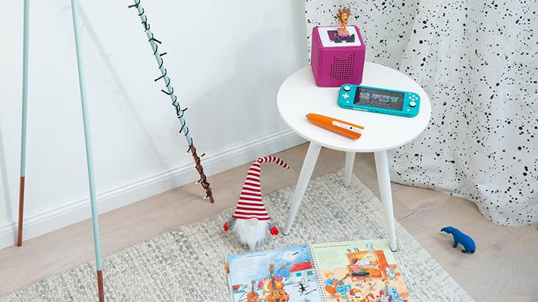 Eine Toniebox, eine Nintendo Switch Lite und ein Tiptoi-Stift auf einem kleinen Tisch.