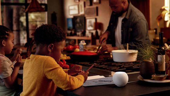Zwei Kinder und eine Person sind in der Küche. Auf dem Tisch steht ein HomePod mini in Weiß.