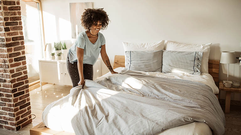Eine Person macht ihr Bett. Die Bettäsche ist Grau-Weiß.