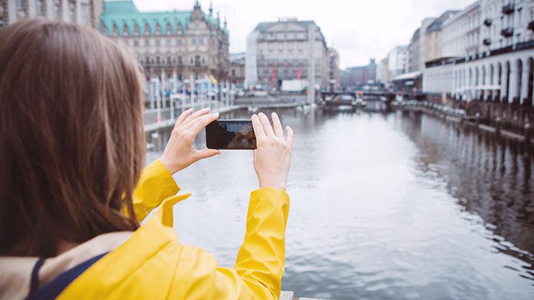 Eine Person hält ihre Smartphone-Kamera auf Gebäude an der kleinen Alster in Hamburg.