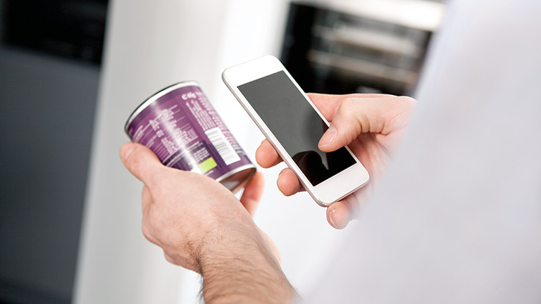Eine Person scannt mit ihrem Smartphone den Barcode auf einer Konservendose.