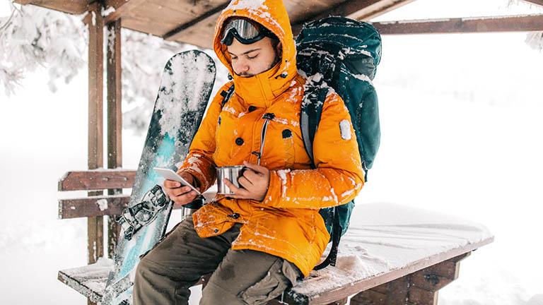 Eine Person sitzt auf einem Tisch und hat ihr Smartphone in der Hand. Daneben steht ein Snowboard.