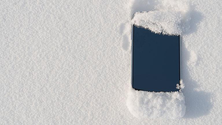Ein Smartphone liegt im Schnee und ist leicht damit bedeckt.