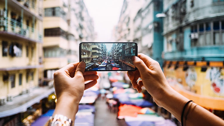 Eine Person hält ein Smartphone in der Hand und macht ein Foto.