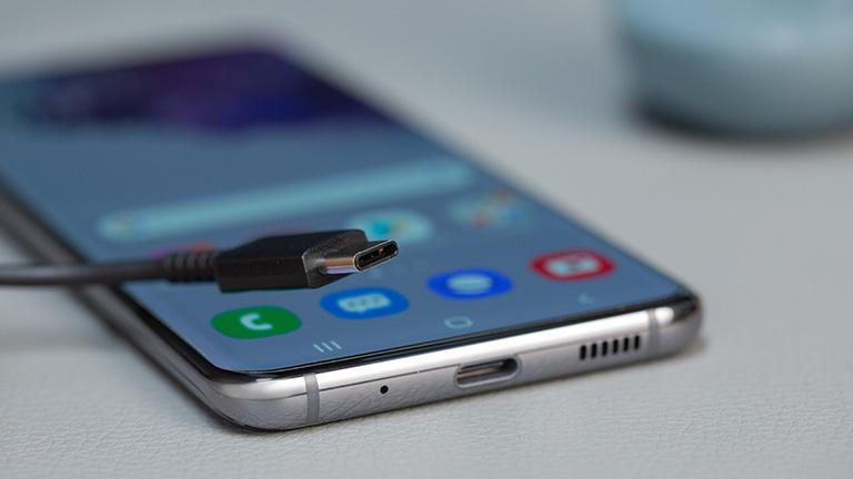 Ein Smartphone mit USB-C-Anschluss und ein USB-C-Kabel.