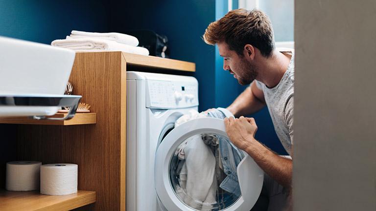 Ein Mann kniet vor einer geöffneten Waschmaschine und steckt Wäsche hinein.