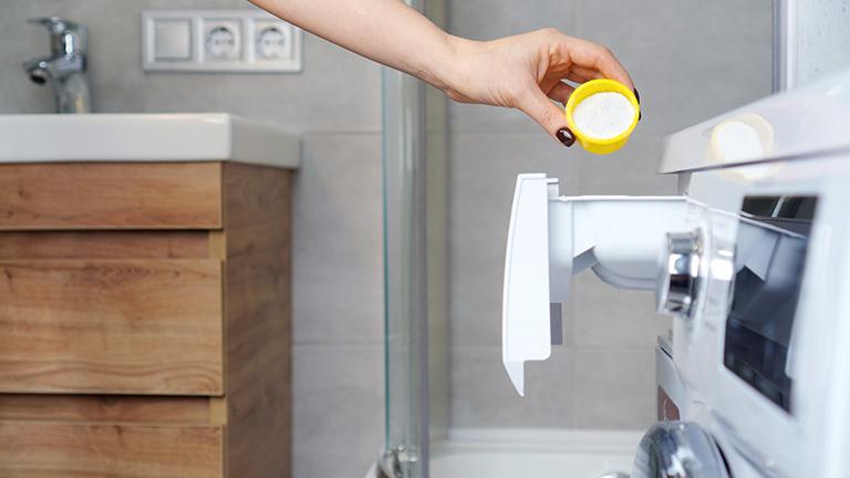 Eine Frauenhand fühlt Waschmittelpulver in die offenen Schublade einer Waschmaschine.