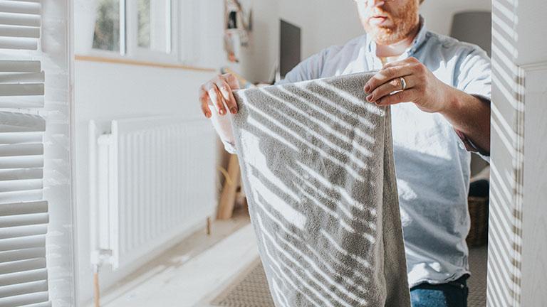 Ein Mann legt ein graues Handtuch zusammen.