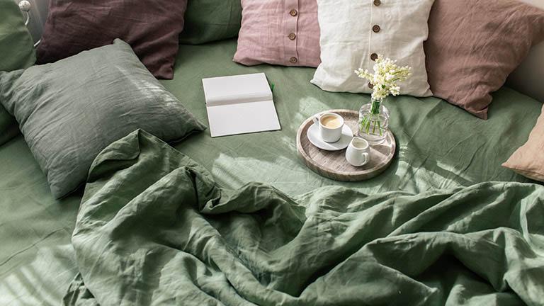 Eine Decke und zahlreiche Kissen auf einem Bett.