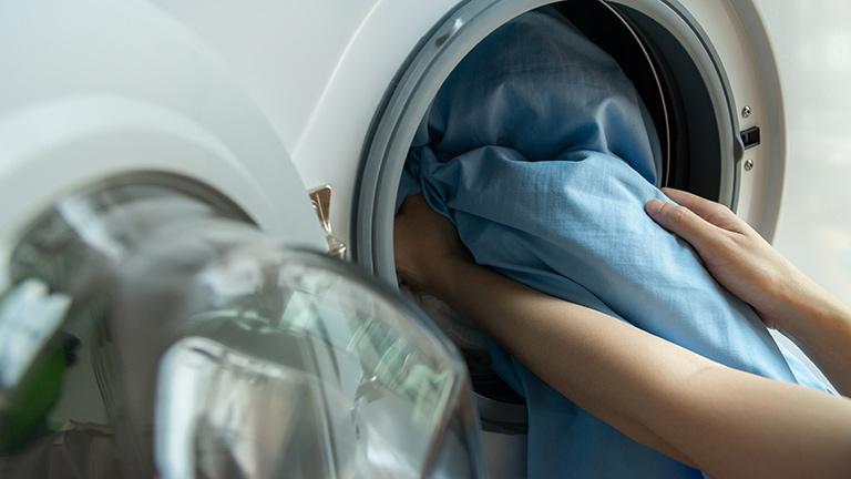Eine Person holt bunte Bettwäsche aus der Waschmaschine.