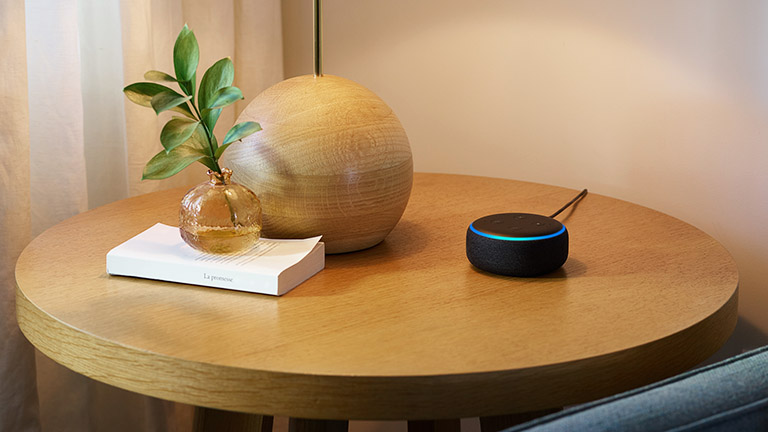Ein Amazon Echo Dot auf einem kleinen Beistelltisch.