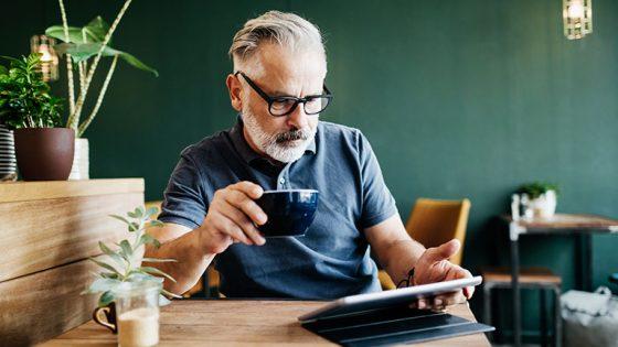Eine Person sitzt in einem Café und bedient ihr iPad.