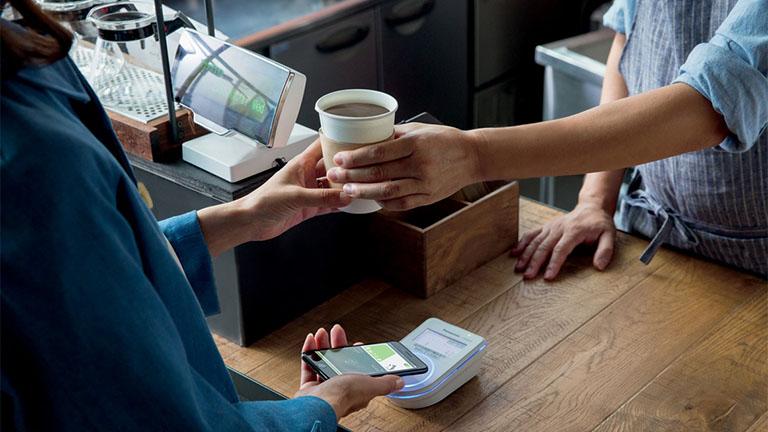 Eine Person kauft einen Kaffee und bezahlt per Smartphone.