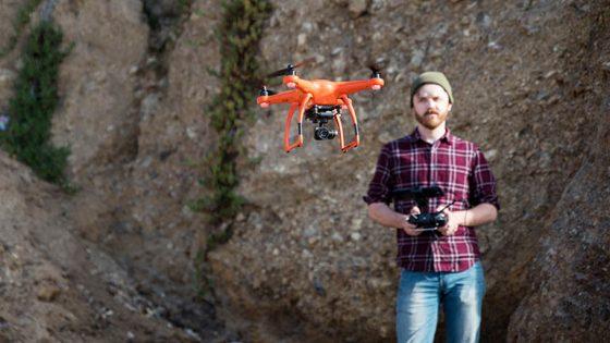 Eine Person hält eine Fernbedienung in der Hand und steuert damit eine im Vordergrund zu sehende Drohne.