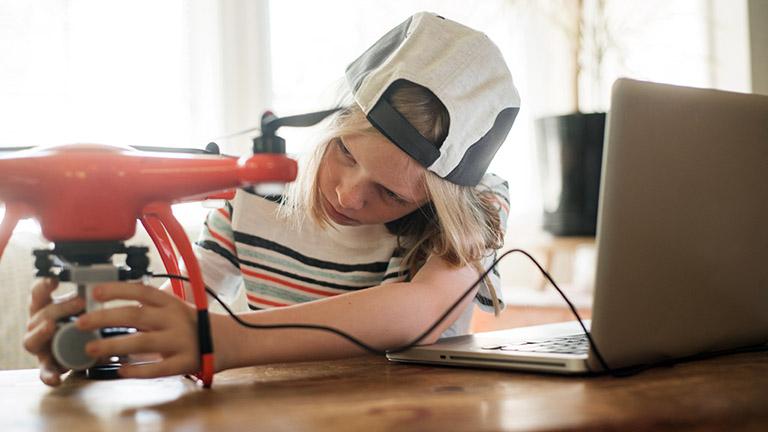 Ein Kind stellt eine Drohne ein, die neben ihm auf dem Tisch steht.