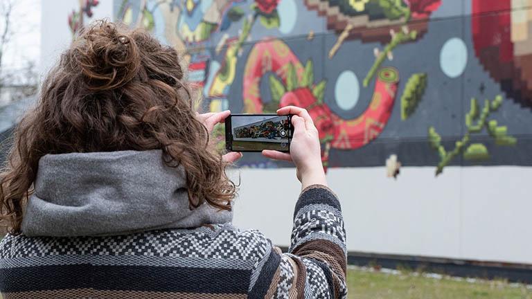 Eine Frau steht vor einer bunten Wand und will ein Foto mit ihrem Smartphone machen.
