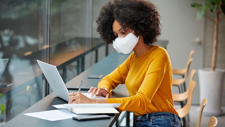 Eine Person trägt die PuriCare-Maske von LG, während sie in einem Büro am Laptop arbeitet.