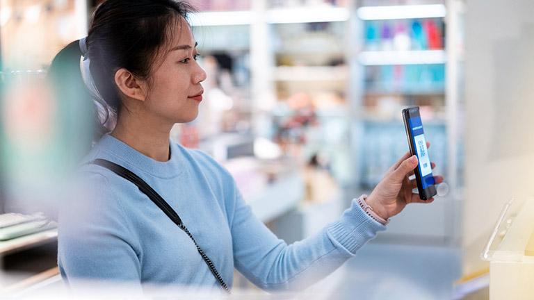 Eine Person hält ihr Smartphone mit Payback Pay in Richtung einer Kasse.