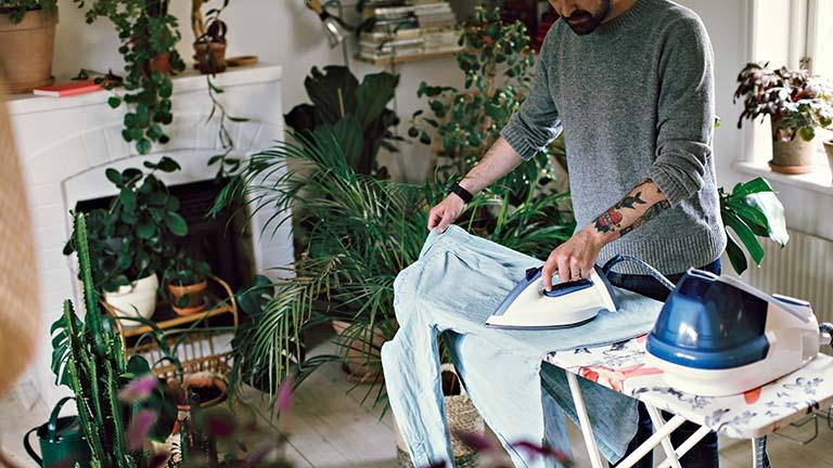 Eine Person steht an einem Bügelbrett und bügelt ein Hemd.