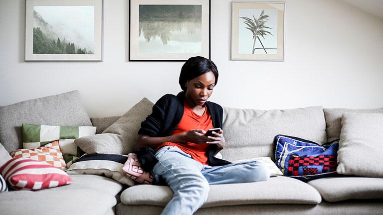 Eine Person sitzt auf dem Sofa und schaut auf ihr Smartphone.