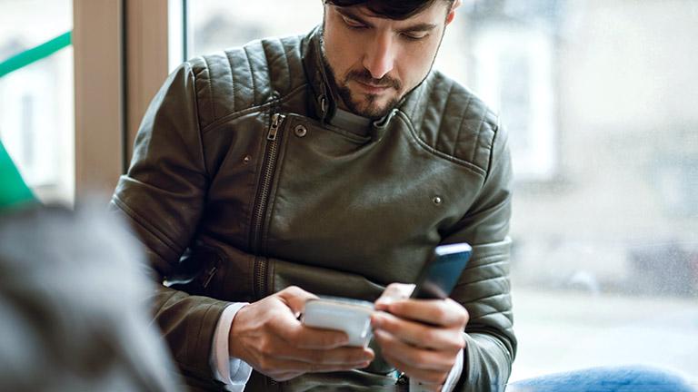 Eine Person hält zwei Smartphones in der Hand.