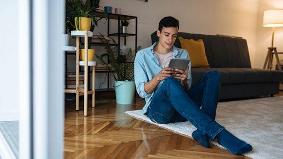 Eine Person sitzt auf einem Teppich und hält ein Tablet in der Hand.