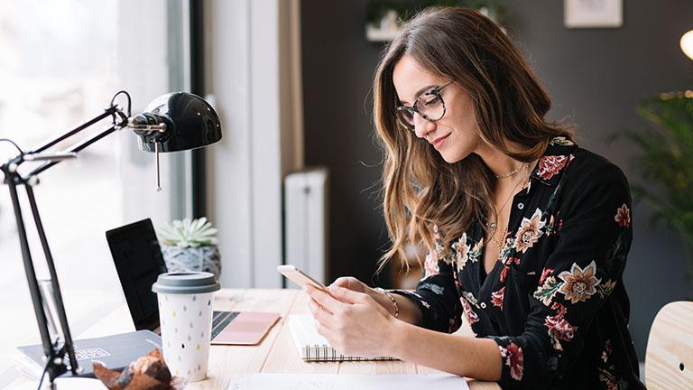 Eine Person sitzt an einem Schreibtisch und hält ein Smartphone in der Hand.