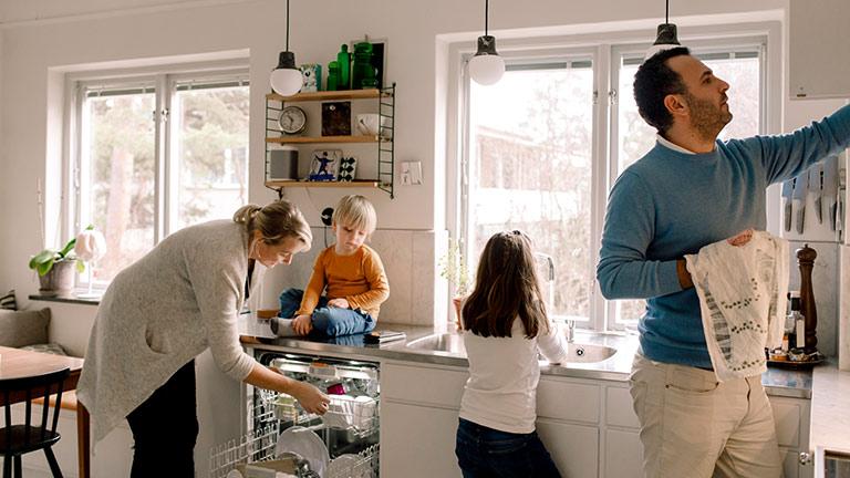Ein Mann, eine Frau und zwei Kinder befinden sich in der Küche. Die Frau beugt sich über den geöffneten Geschirrspüler.