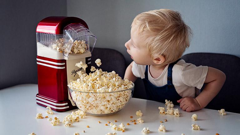 Ein Kind schaut zu, wie eine Popcornmaschine arbeitet.