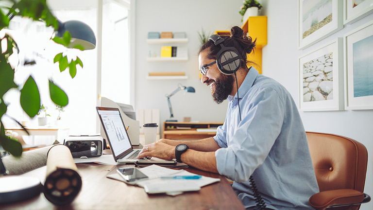 Eine Person sitzt vor einem Laptop an einem Schreibtisch. Er trägt ein Headset.
