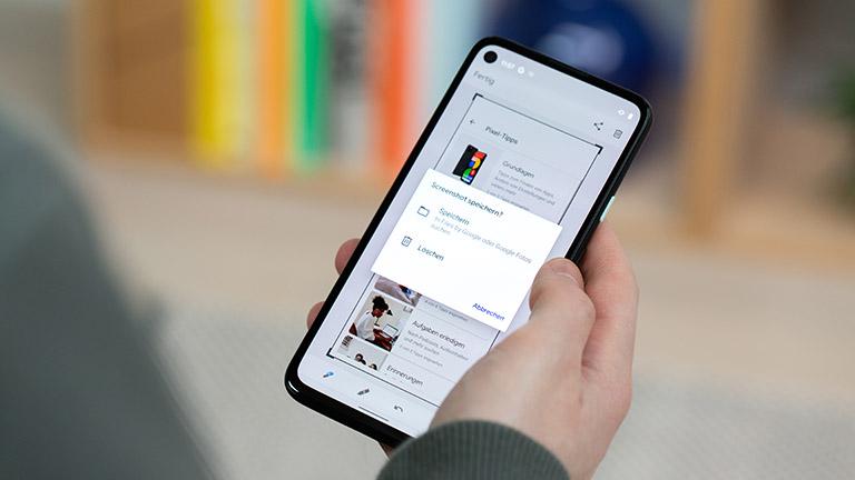 Eine Person hält ein Google Pixel 4a in der Hand. Zu sehen ist eine Einblendung zum Speichern von Screenshots.